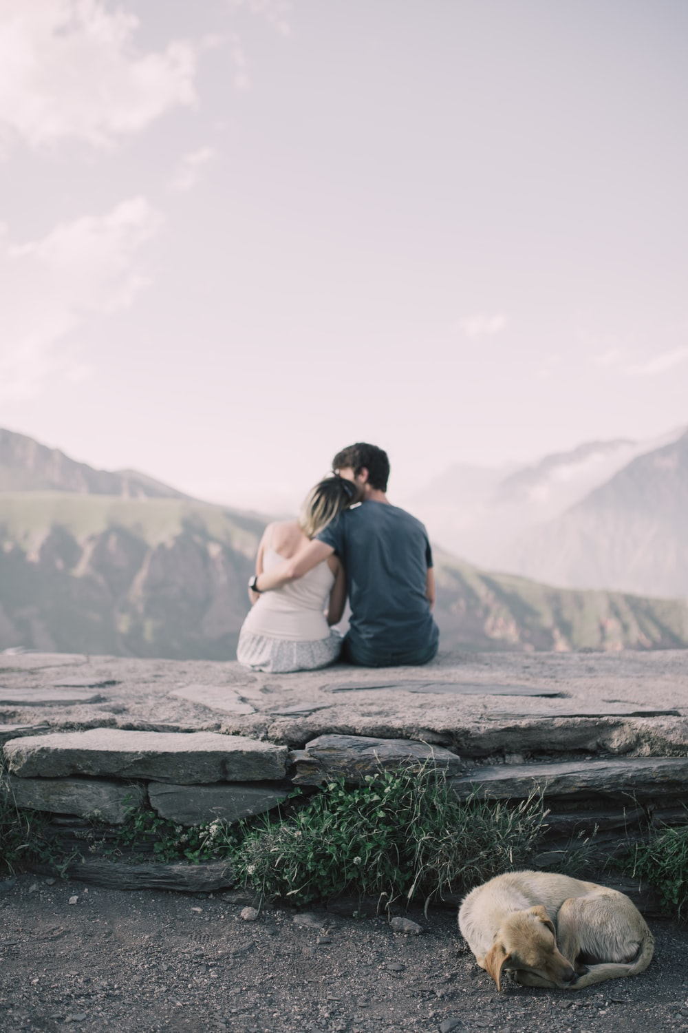 man and woman facing backward while woman's head on man's shoulder on tip of hill