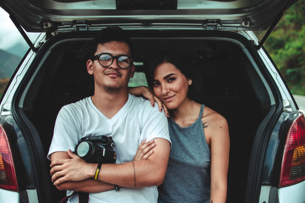 woman leaning on man's shoulder beside car during daytime