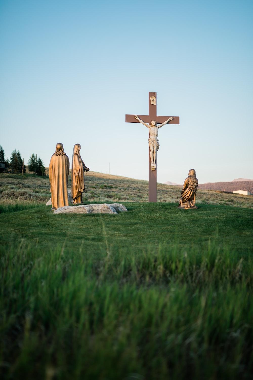 Crucifix statue on green grass