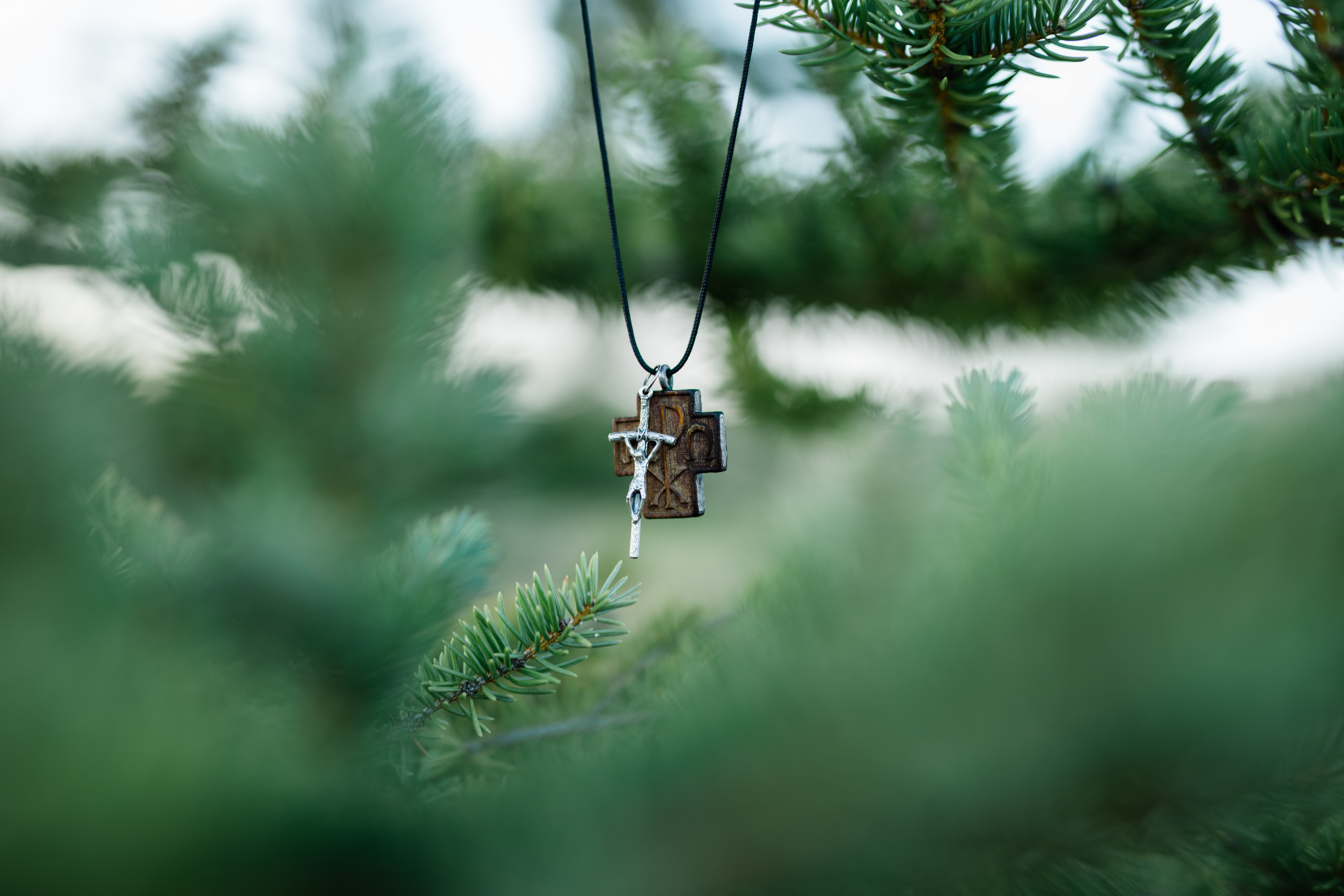 selective focus photography of cross pendant