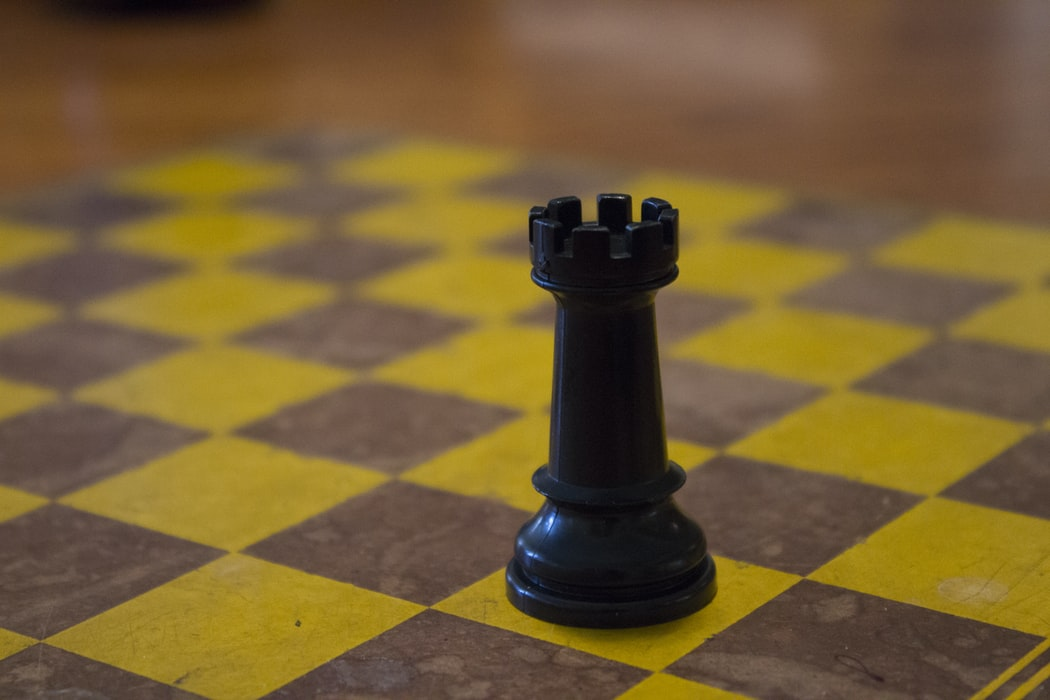 Photo of a black rook on a wooden chess board