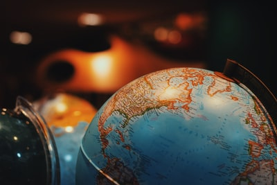 selective focus photo of terrestrial desk globe world teams background