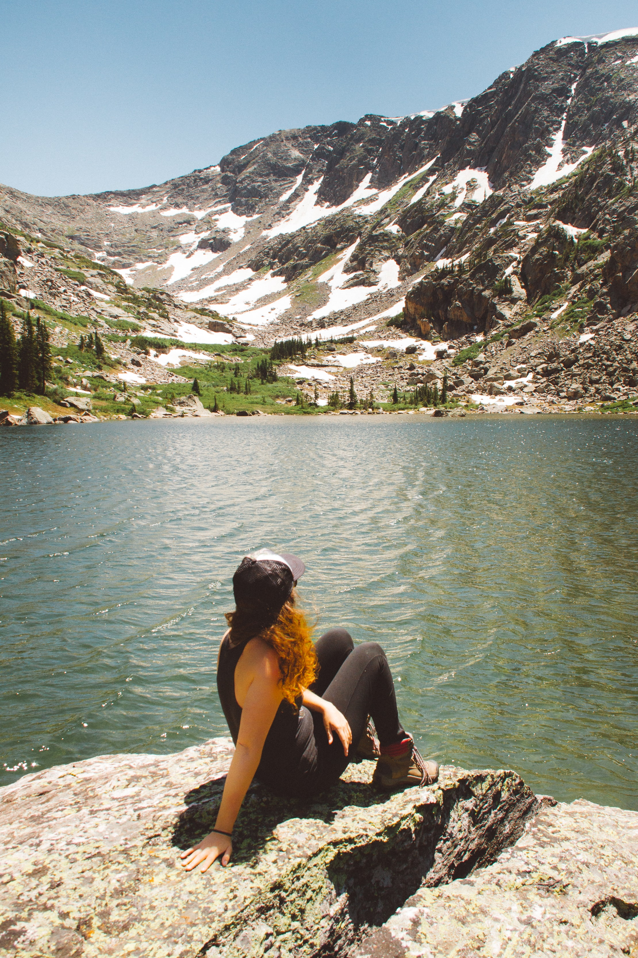 woman sitting on rock formation looking through snowcap mountain near body of water