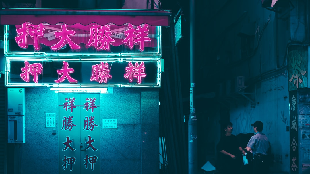 This is one of those shots that just happened by chance. Was walking to the train station when I saw this guy being questioned by a police officer, and then I noticed the neon signs to the left and lined up a composition.