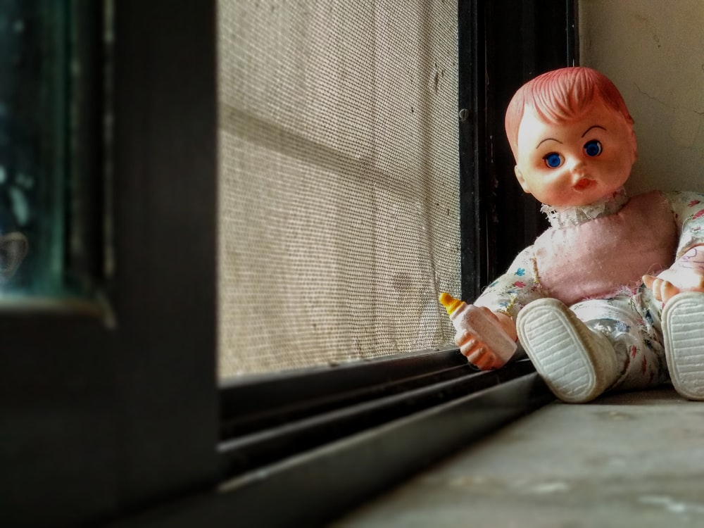 baby doll sitting on window
