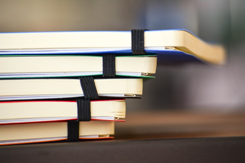 shallow focus photography of stack of book