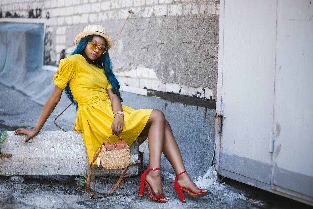 woman in yellow mini dress sitting on concrete slab