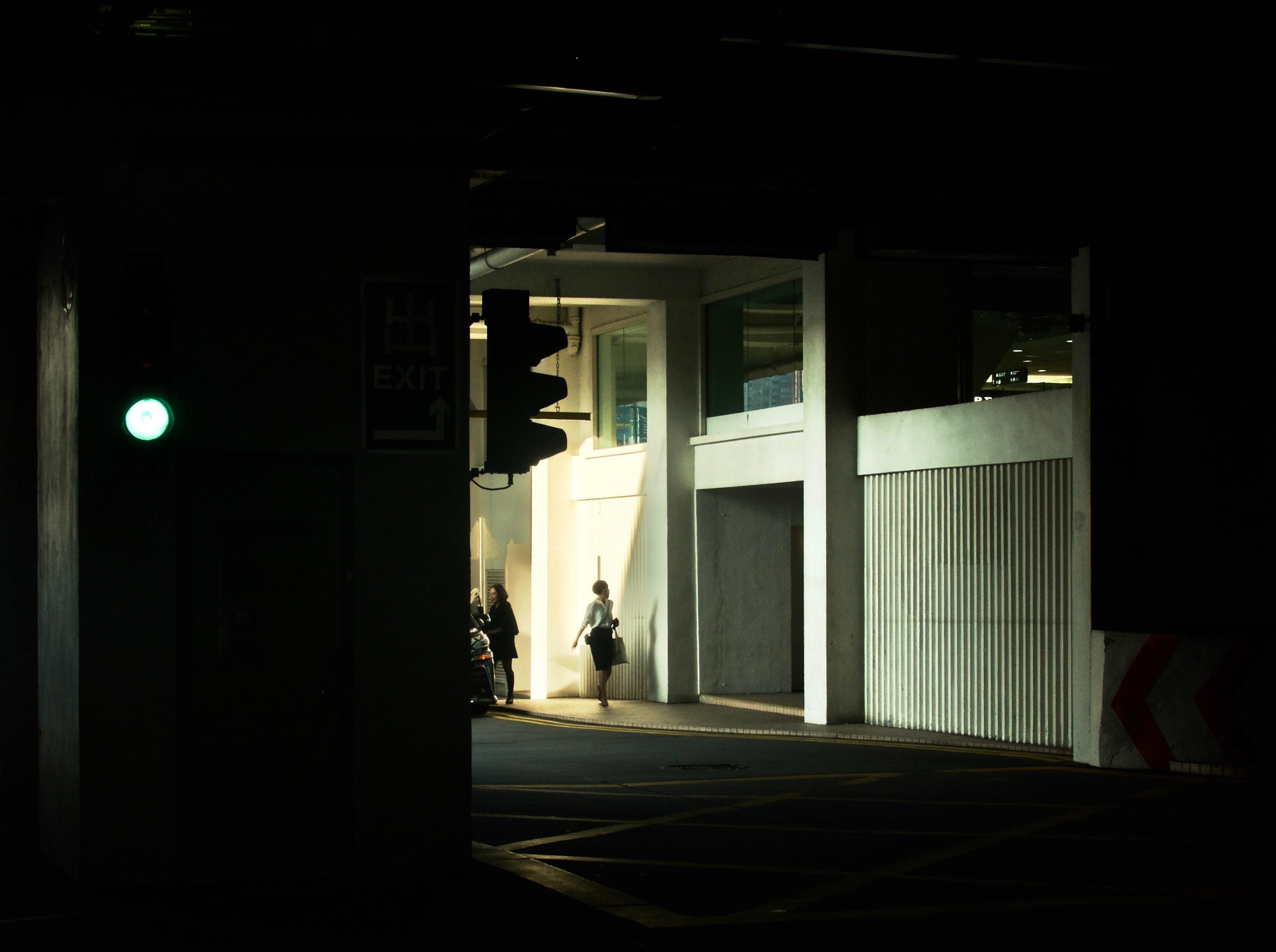 person walking beside concrete wall