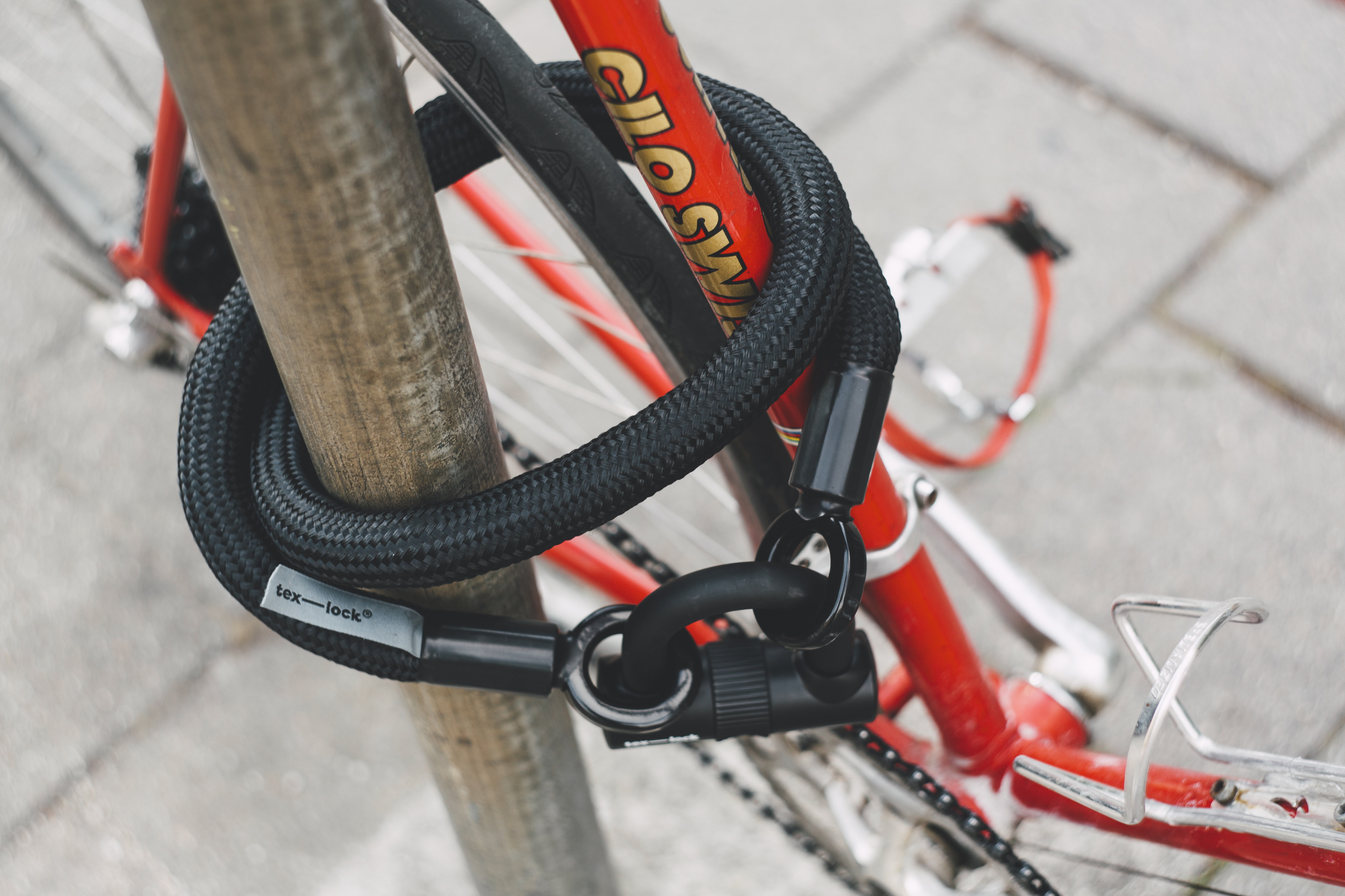 red and white bicycle locked in gray pole