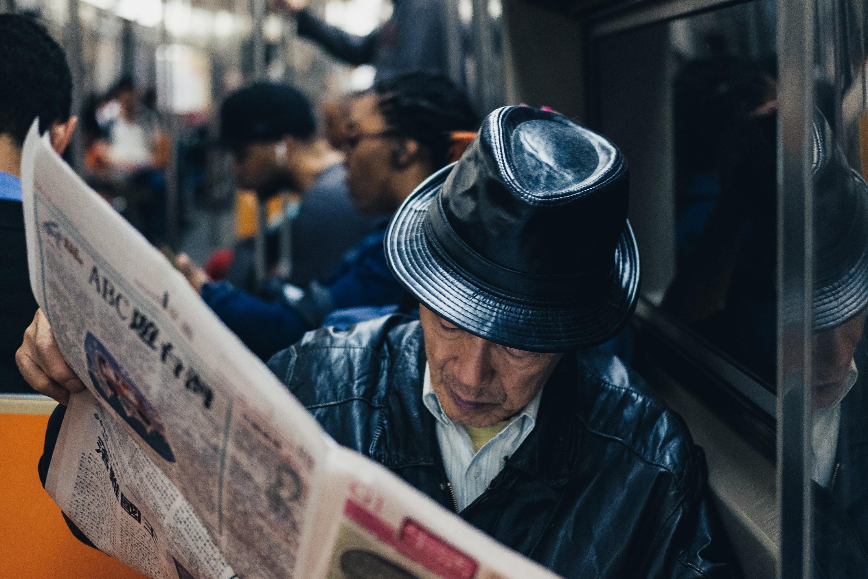 man reading newspaper inside vehicle