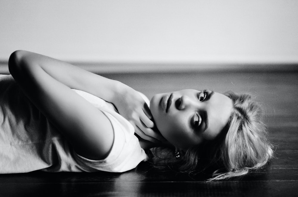 grayscale photography of woman lying on parquet floor