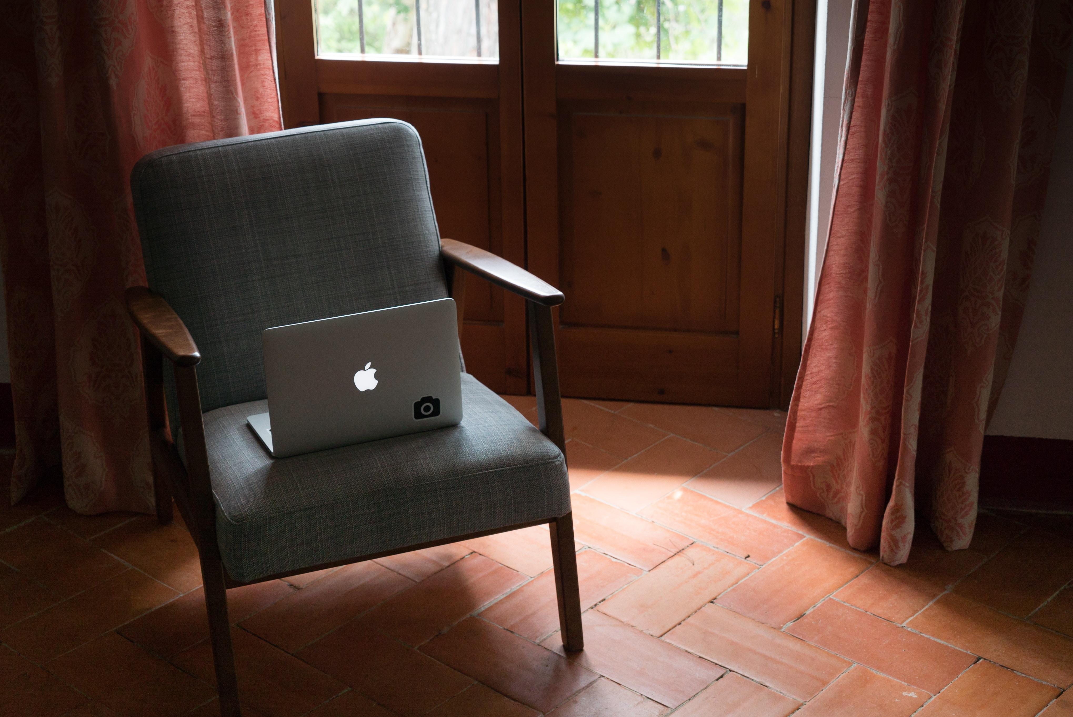 silver MacBook on gray armchair