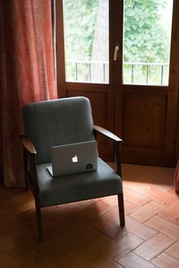 silver MacBook on chair
