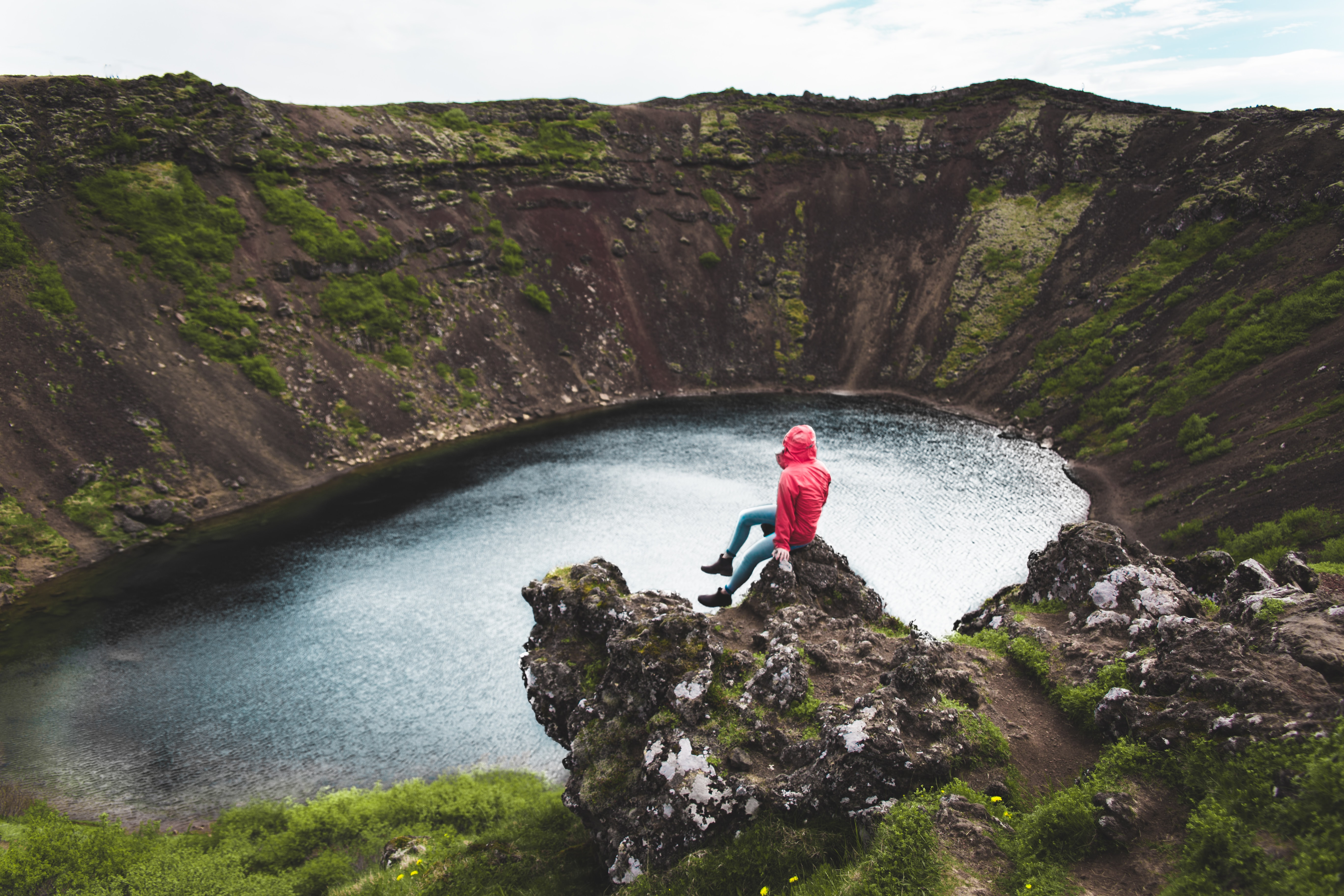 person wearing red hoodie on rock facing body of water