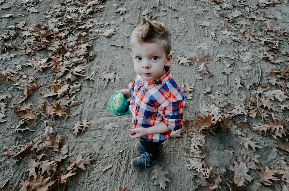 boy in white, blue, and orange plaid button-up shirt holding green cup