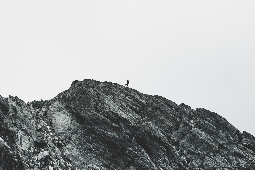 person walking on rock mountain