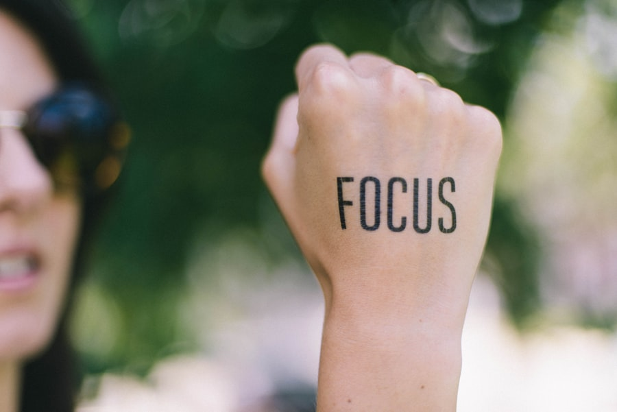 A woman (out of focus) holds up her fist, on which is tattooed the word 'focus'.