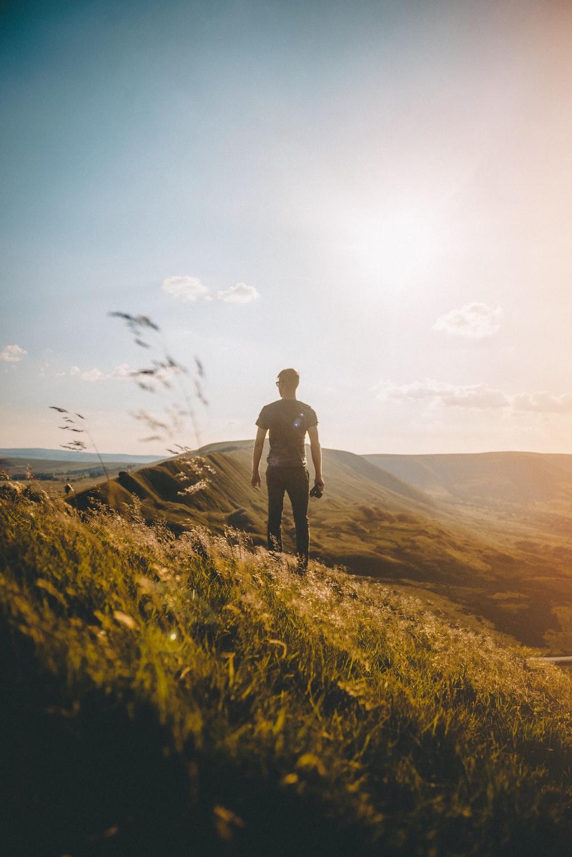 man standing on green grass under blue sky