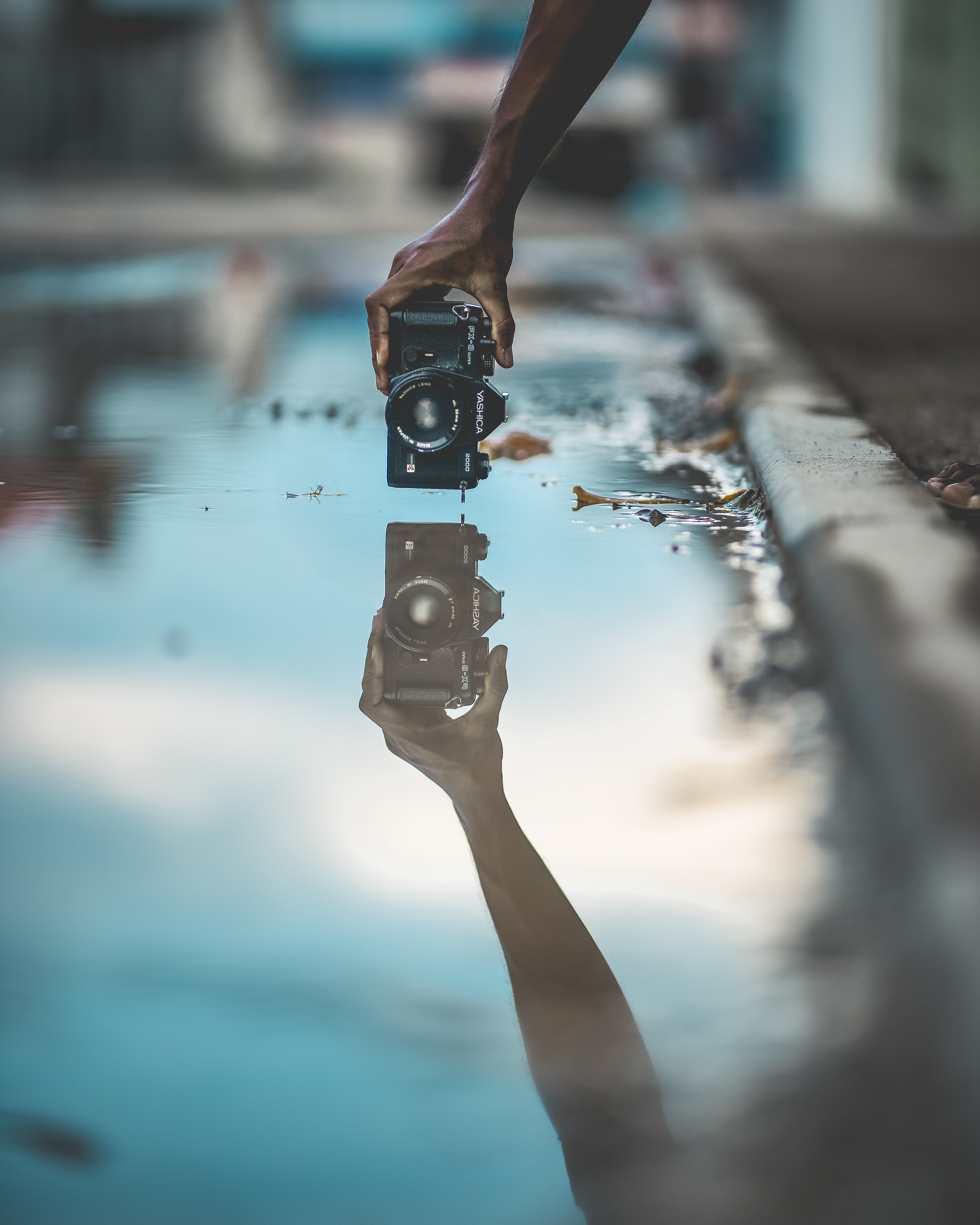 mirror photography of person holding DSLR camera with water reflection