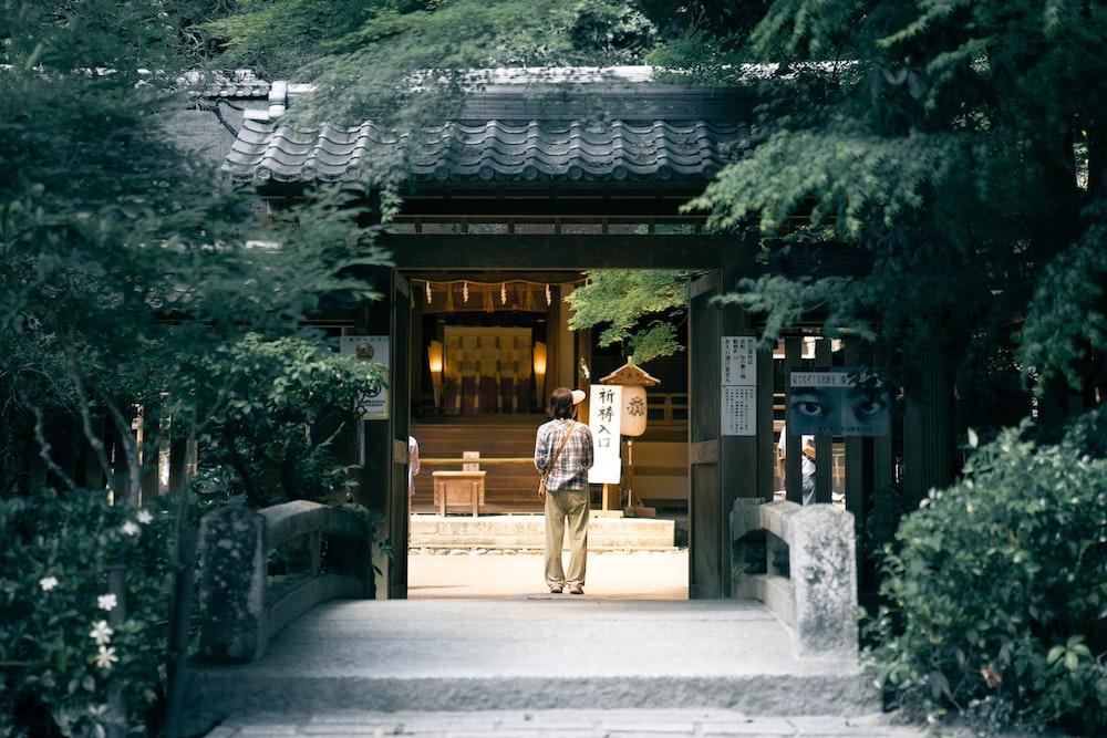 man walking towards brown house