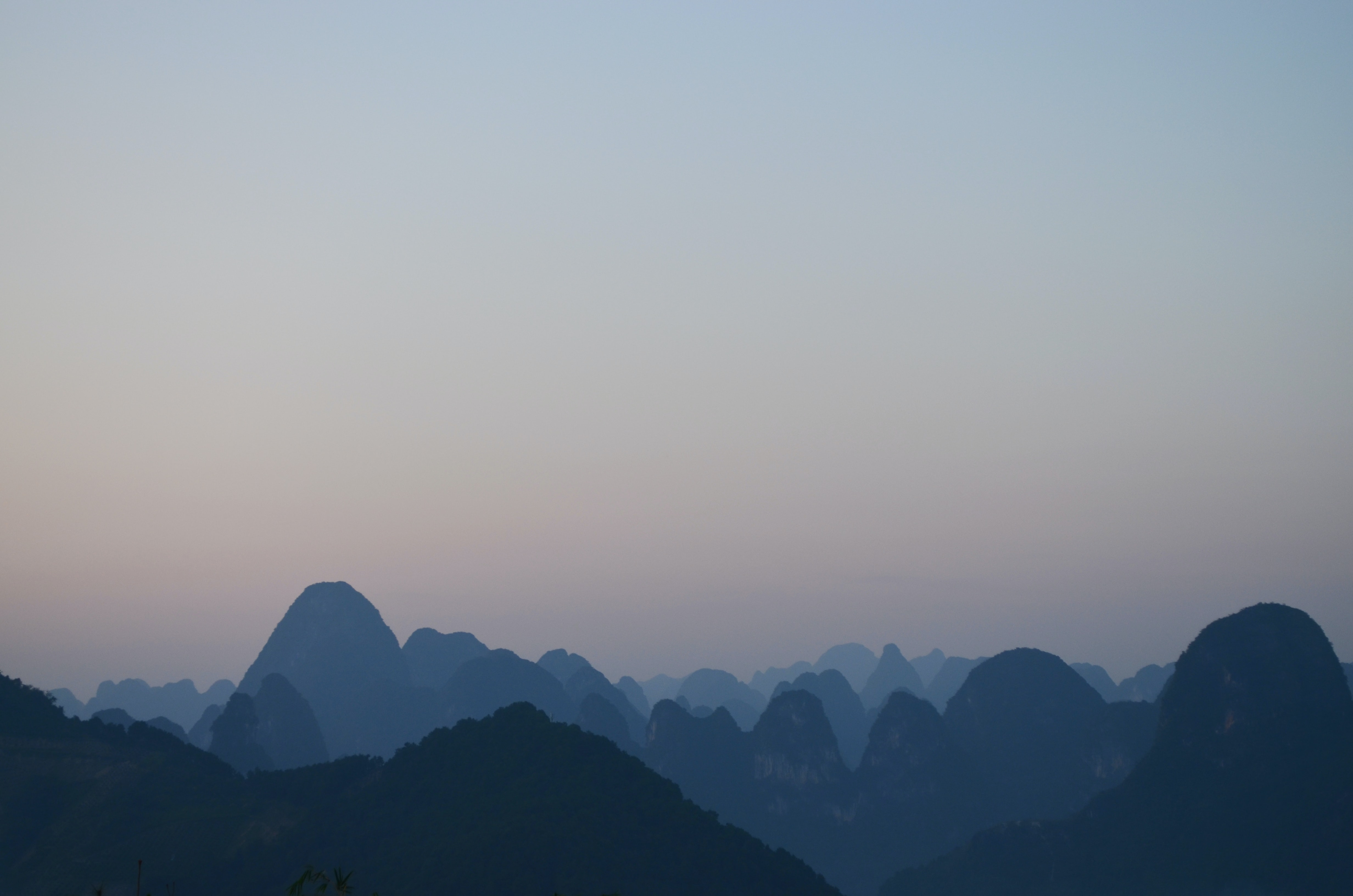silhouette of mountains under gray sky at daytime