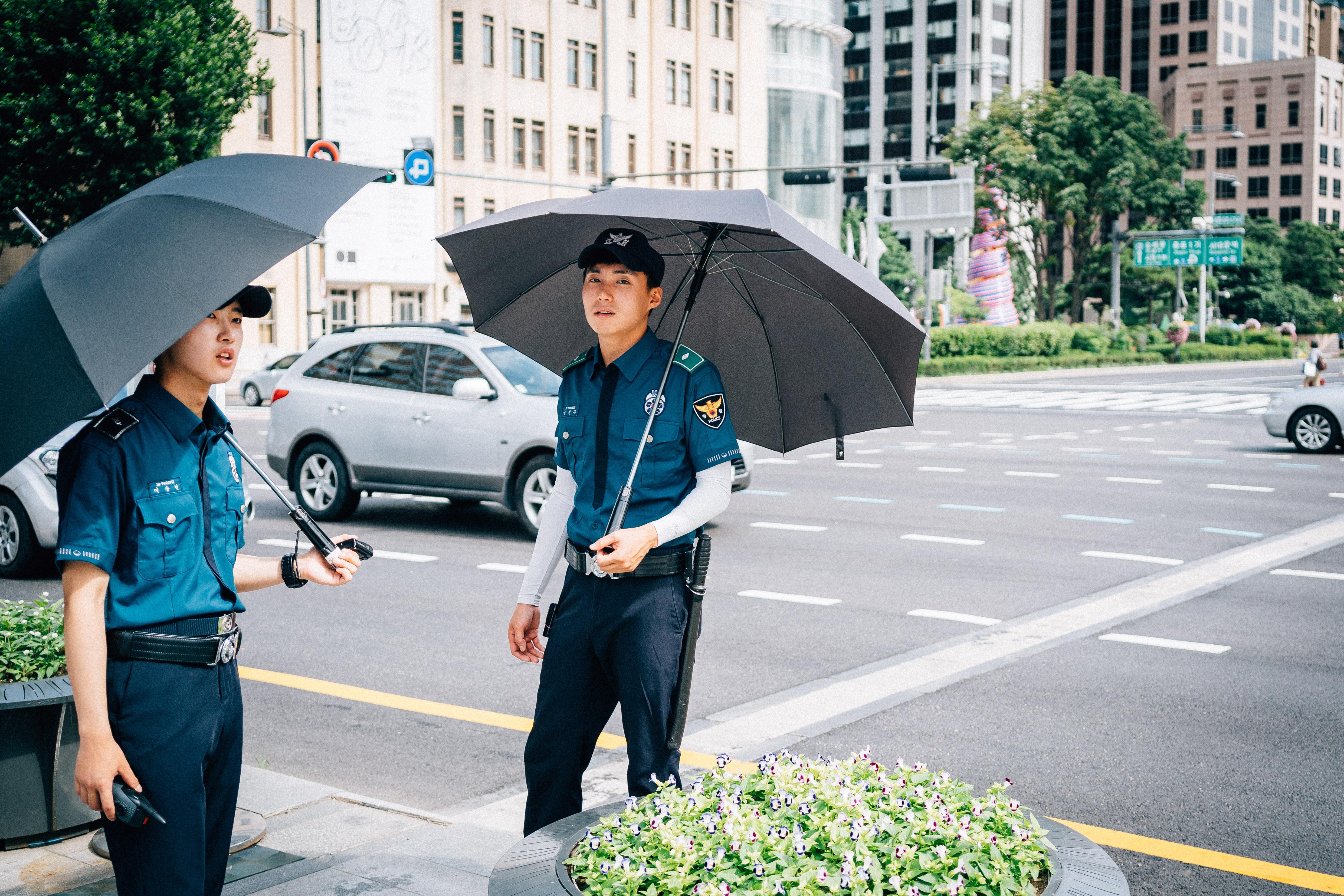 man under umbrella walking on street