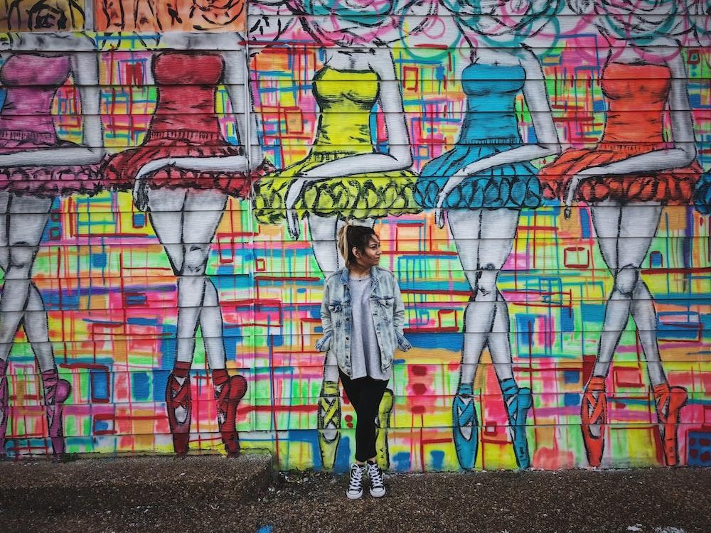 woman standing beside graffiti wall art
