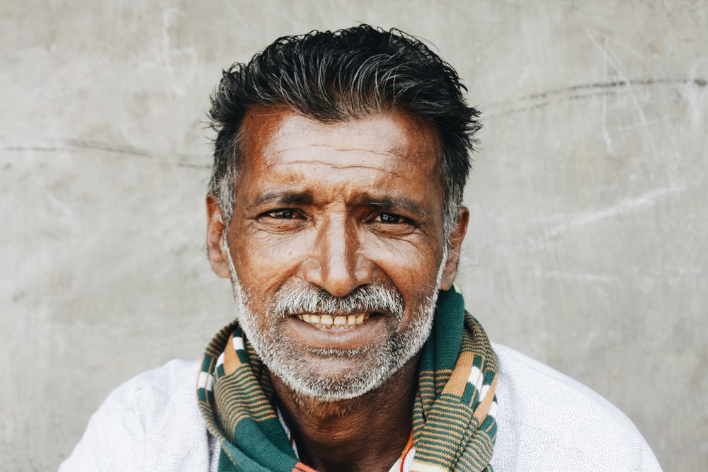 close-up photo of man in white shirt smiling while taking photo