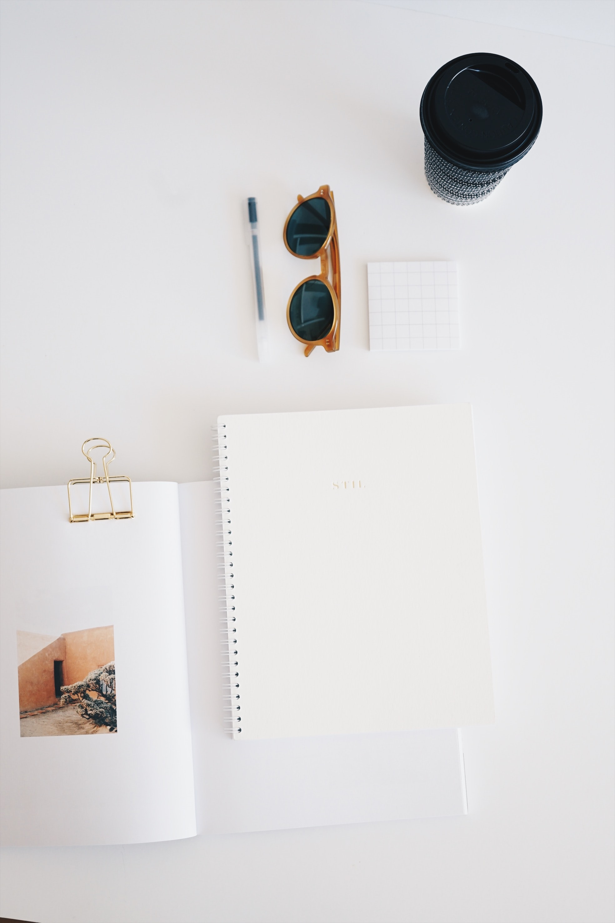 flat lay photography of paper, sunglasses, cup, and pen