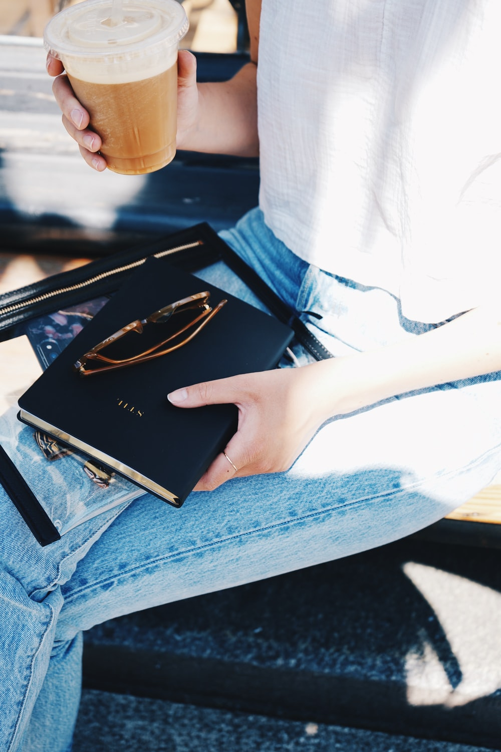 person holding black book and clear plastic disposable cup