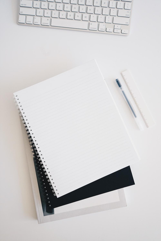 empty spiral notebook near keyboard and pen