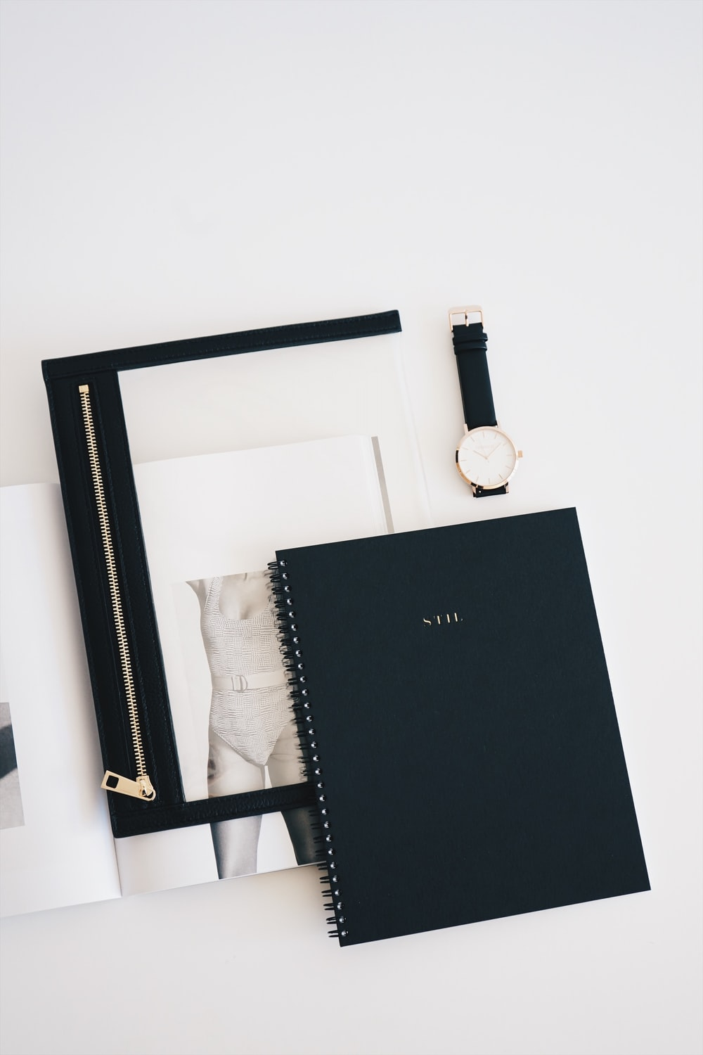 flat lay photo of watch, notebook, and watch