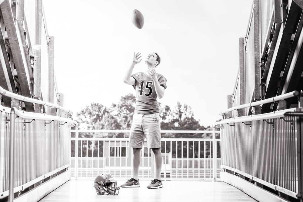grayscale photo of man standing while tossing football outdoors