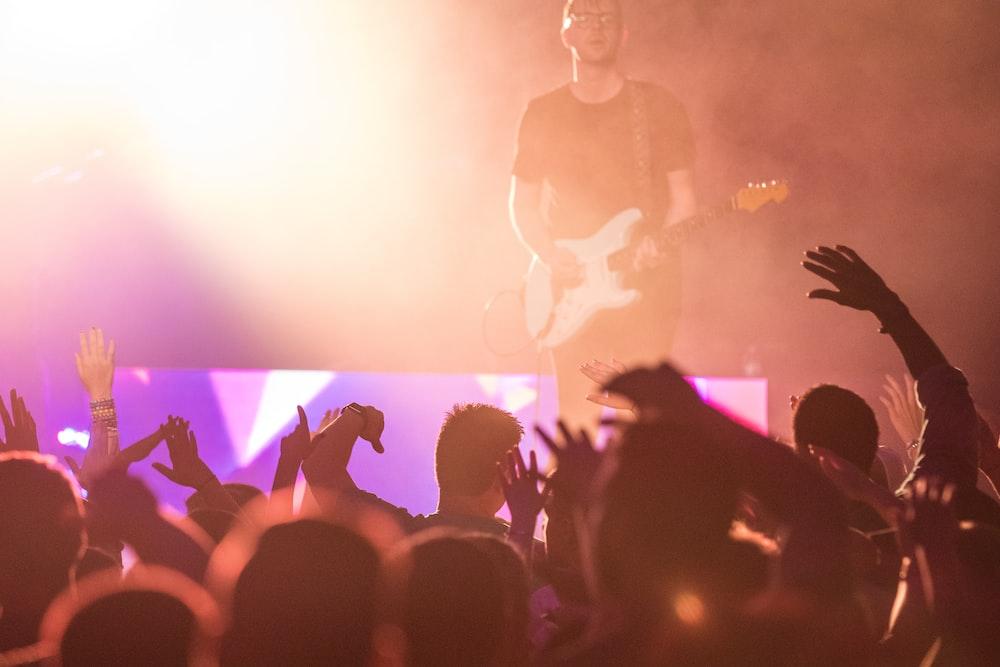 people watching man playing guitar on stage