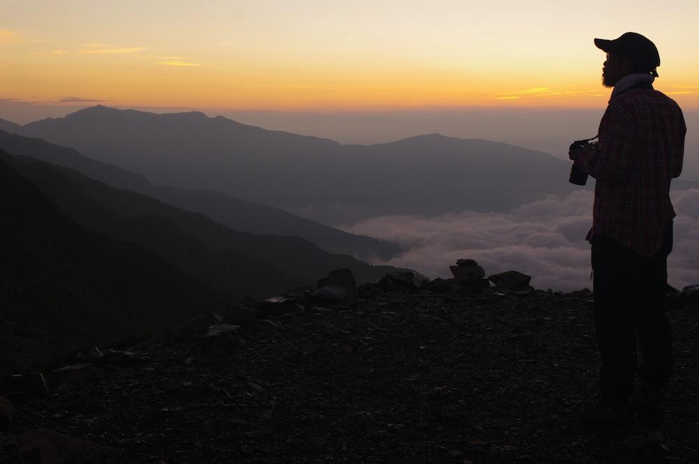 man carrying camera facing sideways looking at the mountain range