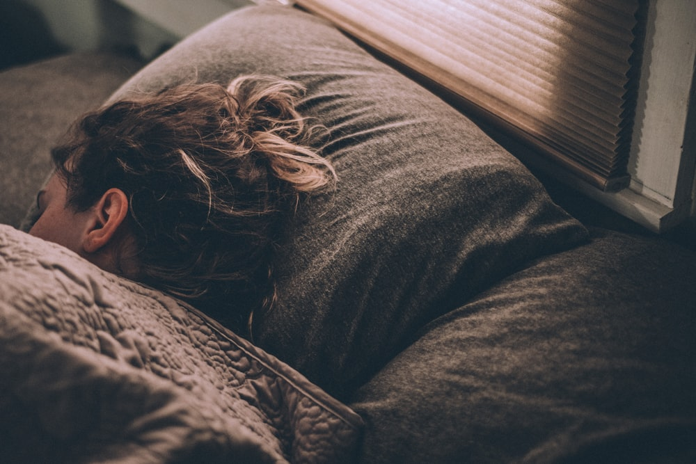 woman sleeping on bed under blankets