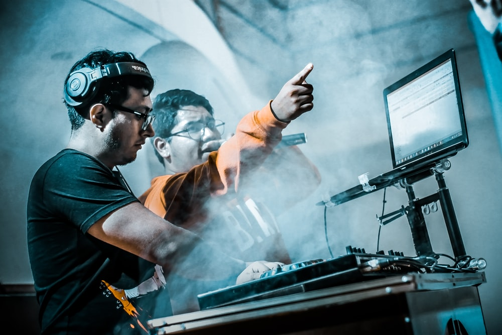 man controlling DJ controller beside man with microphone