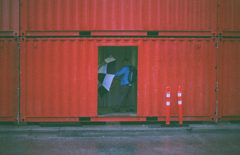 man holding umbrella inside the intermodal container