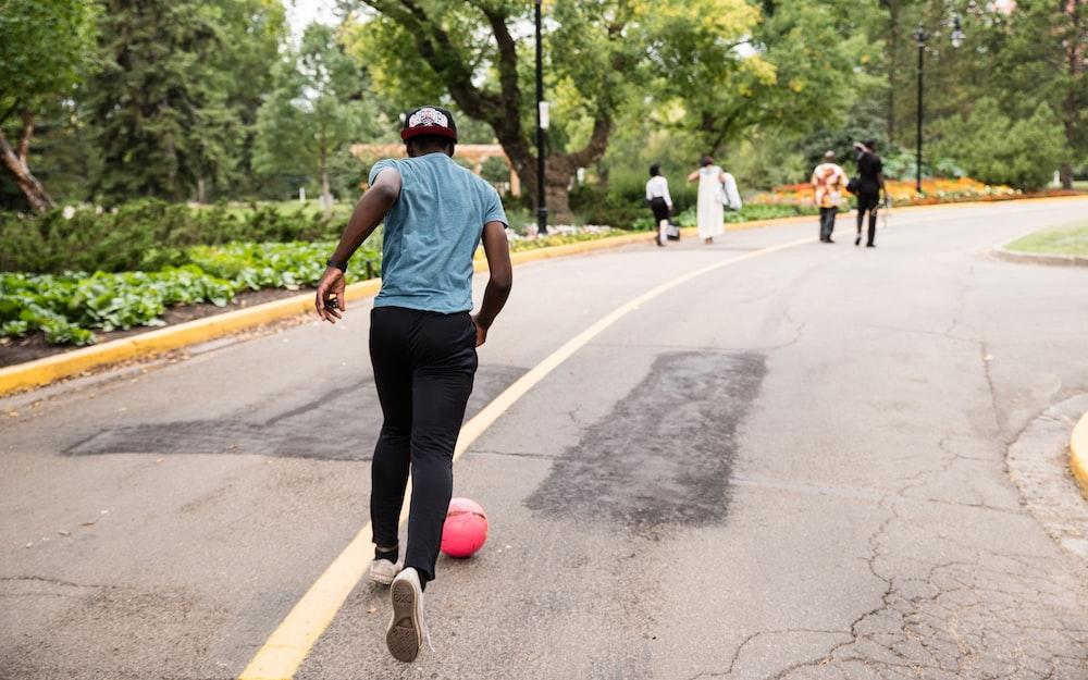 man running behind red ball