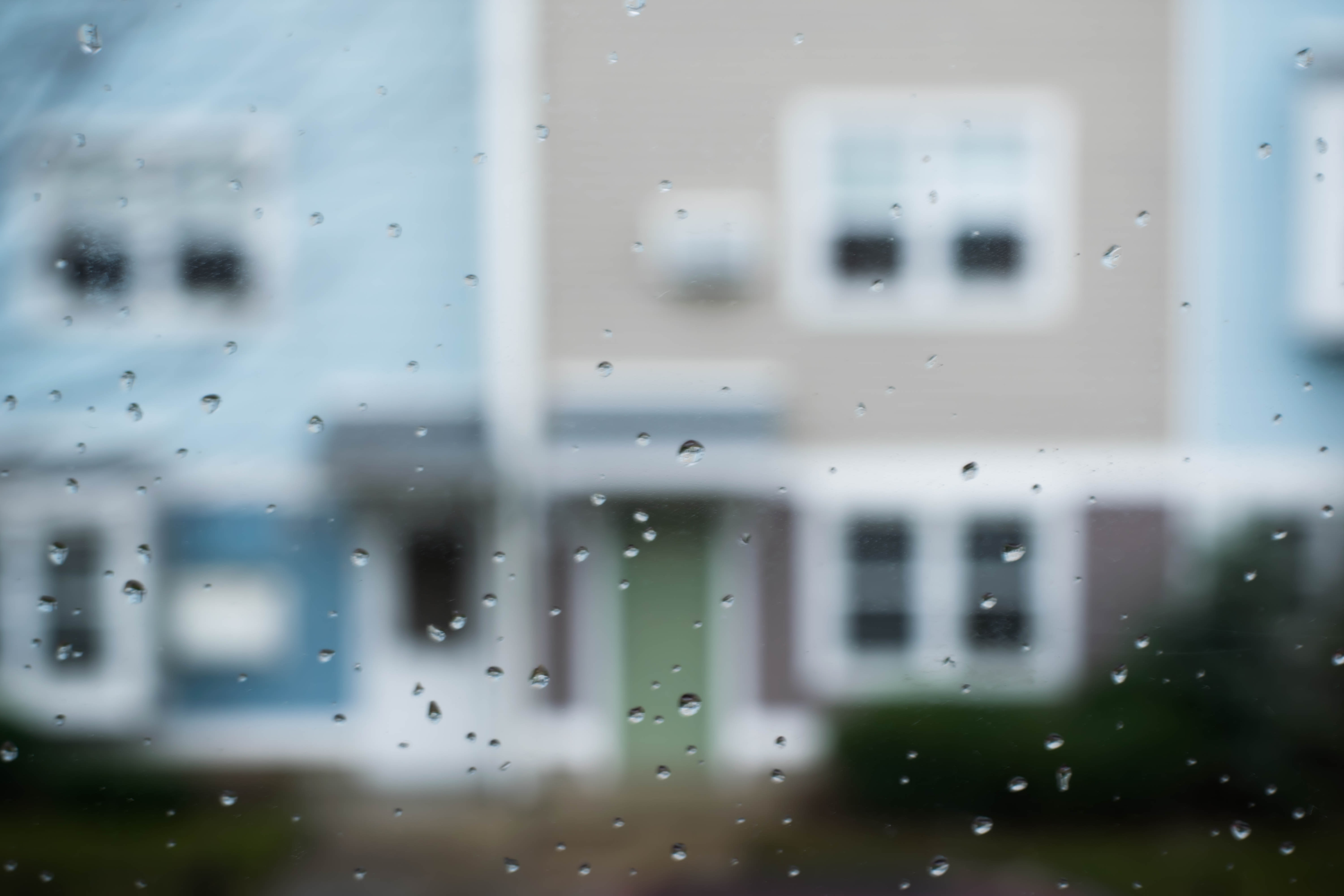selective focus photography of rain droplets on vehicle window