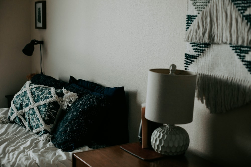 white table lamp on wooden side table