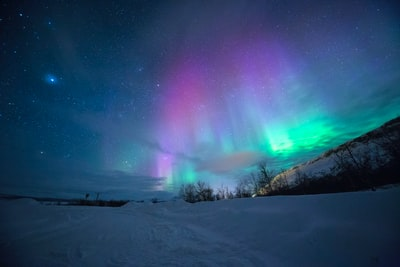 northern lights over snow-capped mountian norway teams background