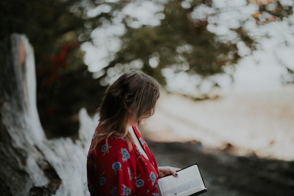 woman holding book on beach