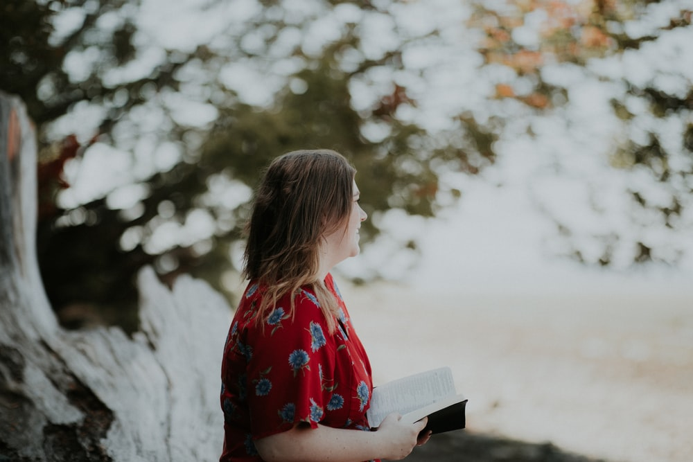 woman holding book outdoors