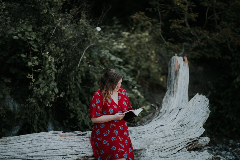 woman reading book sitting on tree log
