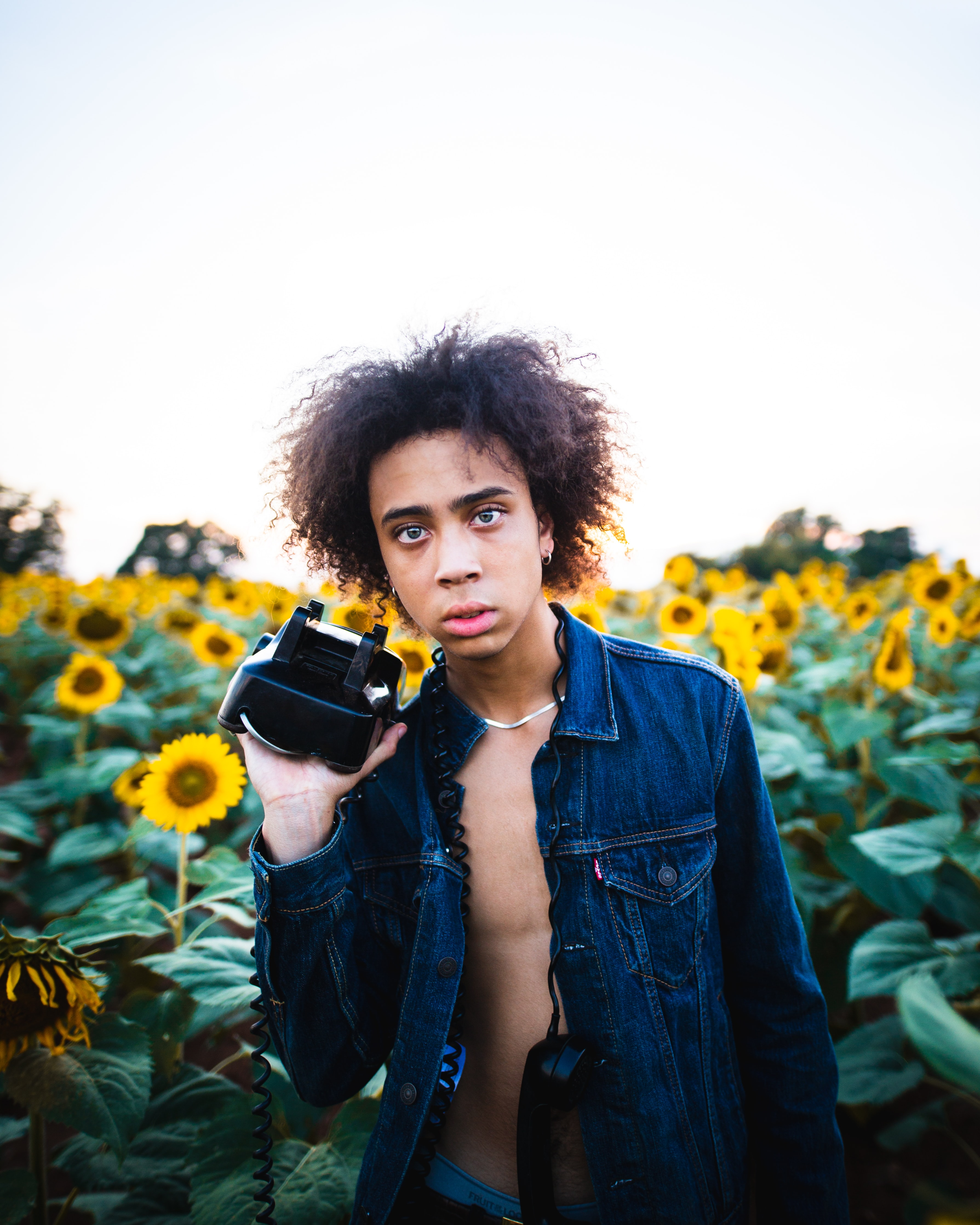 man holding black and white VR headset in front of sunflower meadow