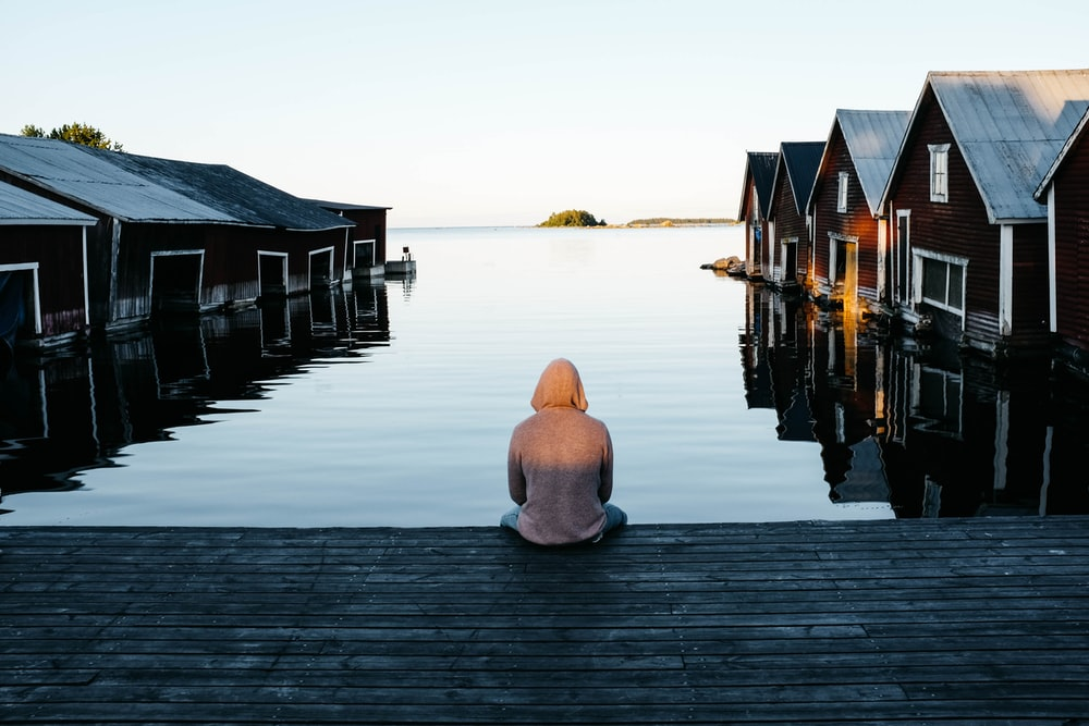 person sitting beside body of water