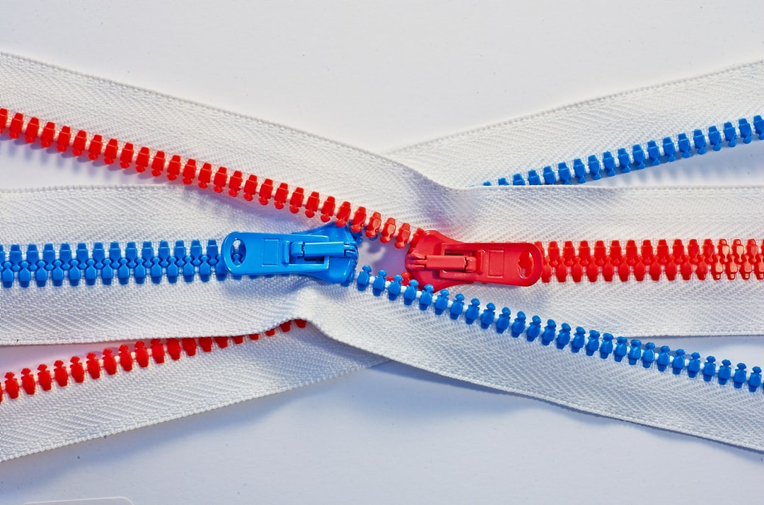 Two intertwined zippers, with blue and red teeth, like male and female, on white background