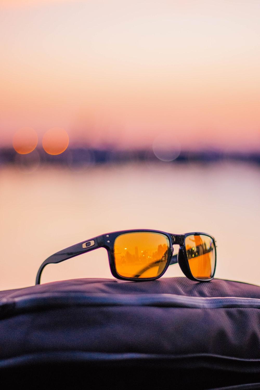black framed Oakley sunglasses with orange lens