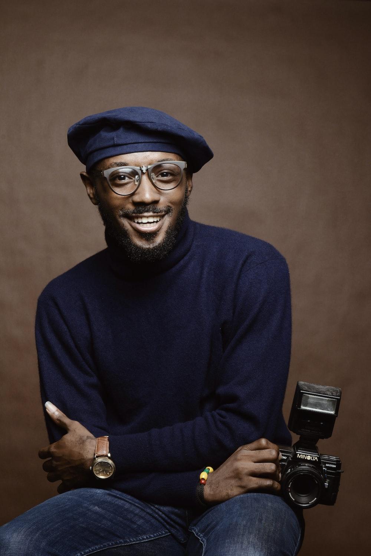 smiling man wearing black turtleneck shirt holding camrea